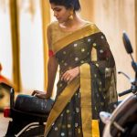 Niranjani Ahathian (9) green saree standing by bike