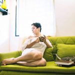 sanya malhotra  in white dress on a green couch with her cat, coffee and books(16)